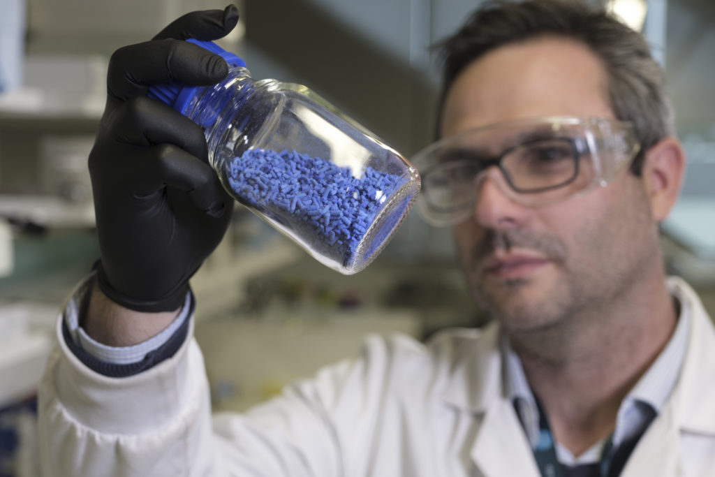 Male researcher in a lab environment examines a jar of blue pellets